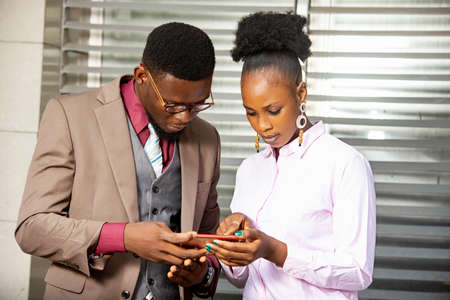two young business partner standing and working with a mobile phone while smiling Foto de archivo