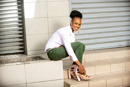 beautiful young woman wearing a white shirt and green jeans sitting on stairs and wearing her heels in front of the camera