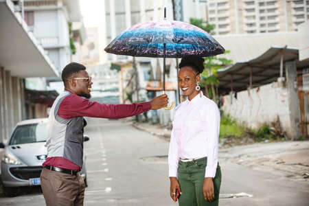portrait of a young man with an umbrella on a young woman on the street outdoors while being smiling