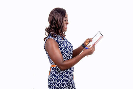 young african woman holding a notebook while smiling; teenage student girl standing on a white background, beautiful beautiful black complexion