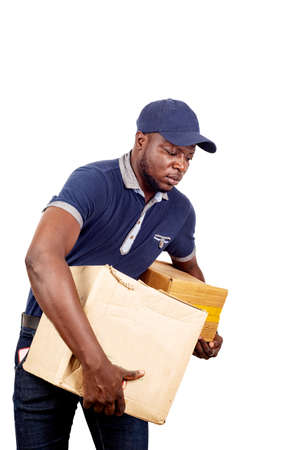 young delivery man standing in hat on white background carrying heavy cardboard boxes. .