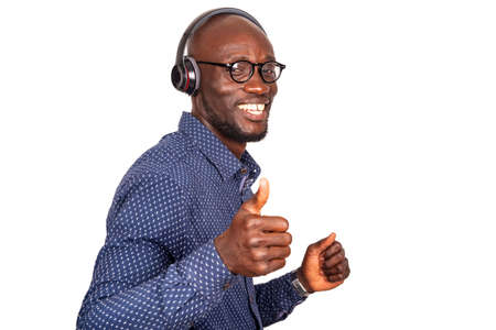 Young man listening to music with white headphones on isolated background, making a thumbs up happy gesture with hand. Approve the expression by looking at the camera successfully. Stock fotó