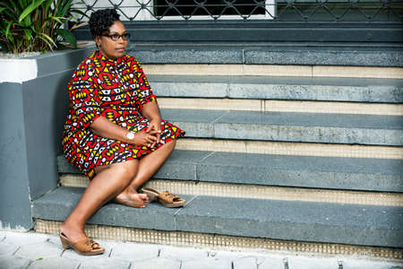 beautiful mature woman wearing eyeglasses sitting on stairs and looking aside