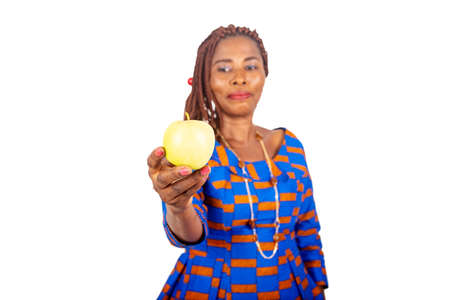 beautiful adult woman wearing a traditional loincloth giving a fresh yellow apple