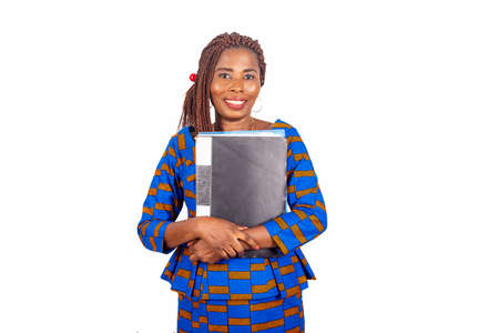 beautiful african businesswoman in traditional dress standing on white background wearing a notepad and looking at camera smiling