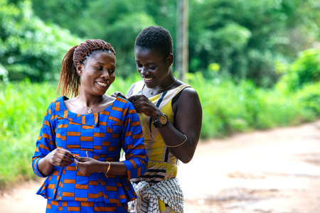 beautiful african woman standing in the countryside helping her sister to wear a neck jewel smiling.