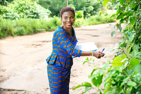 beautiful adult businesswoman standing in nature holding a document with a green leaf and looking aside smiling.