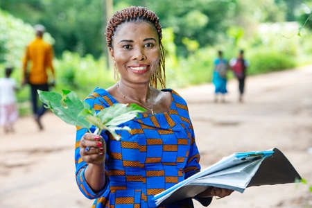 beautiful adult business woman standing in nature holding green leaf petals with document in hand.