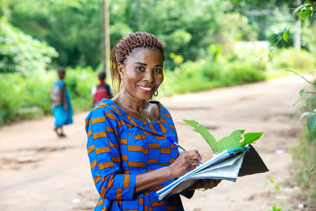 beautiful adult business woman standing in nature writing in a document and looking at camera smiling.