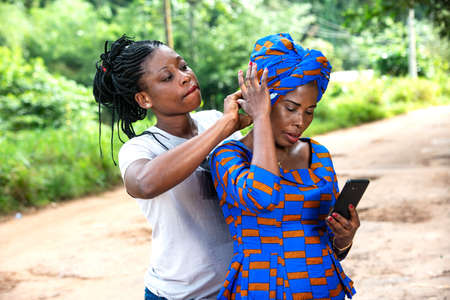 woman in white clothing tying the scarf on the woman's head in traditional loincloth with the help of a mobile phone.
