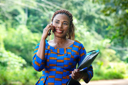 beautiful adult businesswoman standing talking on mobile phone and holding documents smiling.