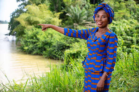 beautiful adult business woman standing in the park and pointing with finger at the lake, river smiling. Banque d'images