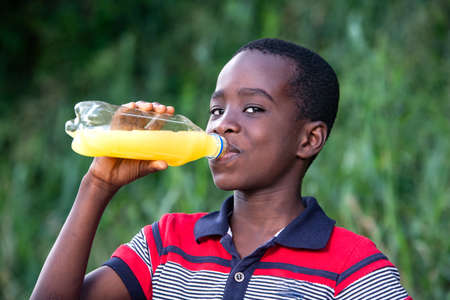 a young boy in a t-shirt standing in a park drinking fruit juice and looking at the camera smiling. Banque d'images