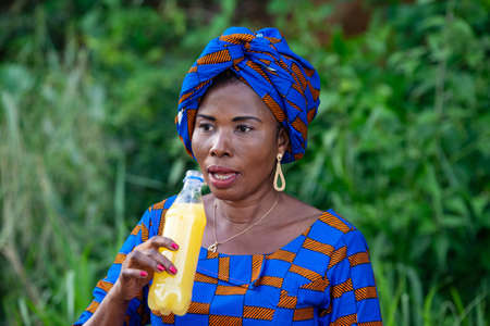 a beautiful mature african woman in traditional dress standing in the countryside talking by holding a bottle of fruit juice.