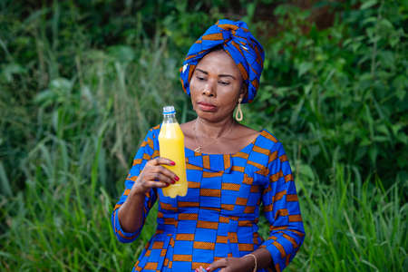 a beautiful mature african woman in traditional dress standing in the countryside looking at a bottle of fruit juice