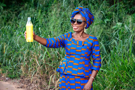 a beautiful mature african woman in traditional dress standing in the countryside showing a bottle of fruit juice smiling