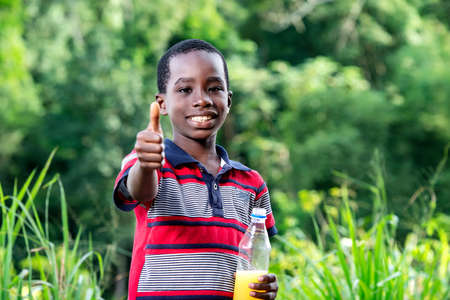 A young boy in t-shirt standing in a park with a bottle of fruit juice making thumb gesture and looking at the camera smiling.