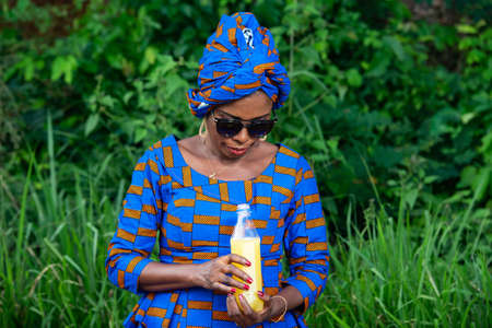 a beautiful mature african woman in traditional dress standing in the countryside looking at a bottle of fruit juice.