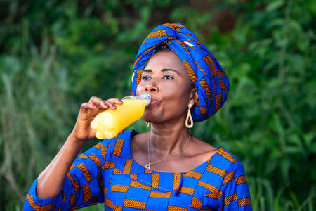 a beautiful mature african woman in traditional dress standing in the countryside drinking fruit juice.