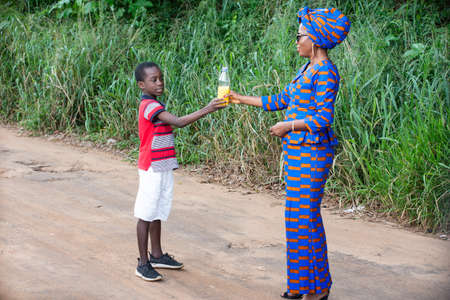 a beautiful mature african woman in traditional dress standing in the countryside giving a bottle of juice to her son smiling.