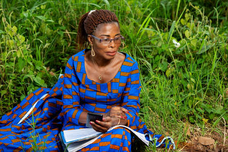 a beautiful mature businesswoman in traditional dress sitting in a park with a document and holding mobile phone and thinking about it.