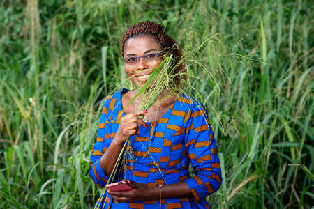 a beautiful woman in traditional clothes standing in a park holding herbs and mobile phone and looks at the camera smiling.