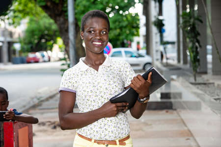 a beautiful young businesswoman in t-shirt standing outdoors holding documents and looking away smiling