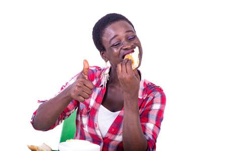 beautiful young woman sitting at the table eating a piece of bread with her eyes closed, showing her thumb.