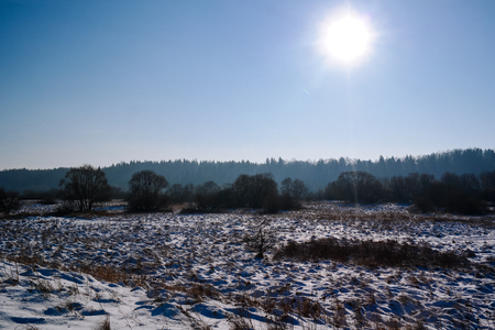 Winter field covered with snow with traces on the snow. Sunny day in the winter Imagens