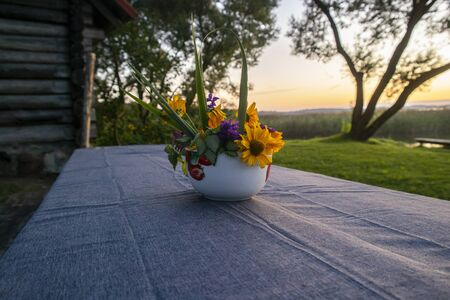 Bouquet wildflowers. Outdoors on a vintage table. As the sun sets. Reklamní fotografie