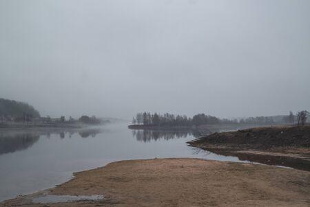 Abandoned place landscape, early morning fog. Calm water, misty lake background.