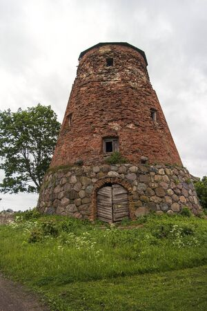 Abandoned ruin of old windmill tower near the city.