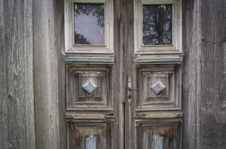 Old gray threadbare wooden door in an old house. East Europe