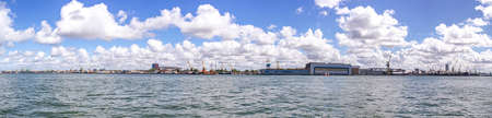 Panorama of heavy harbor jib cranes and ships on the pier in the Klaipeda Sea Port, beautiful clouds on the summer sky Imagens