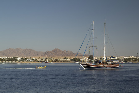 seaside town: wooden yacht in the bay with a seaside town and mountains in the background