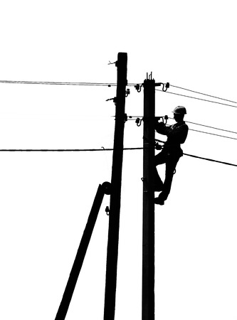 silhouette of an electrician in casque works on a pole