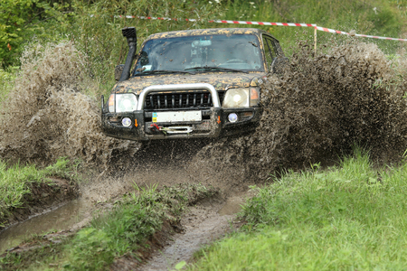 toyota: UKRAINE - JULY 28 - Toyota Land Cruiser Prado breaks overcomes the water obstacle with splashes of mud during a race on July 28, 2015 in Ukraine. Editorial