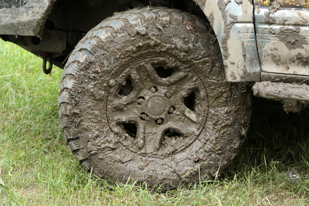 very dirty: very dirty wheel of a four-wheel drive stands on a green grass