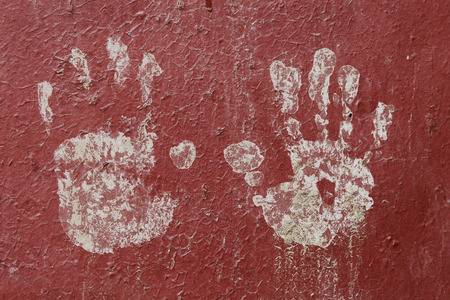 babyhood: texture of white childrens handprint by white paint on a red metallic fence