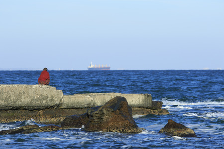 solitariness: single woman dressed in red sits back lonely on the ruined pier in Black Sea with ship on the horizon