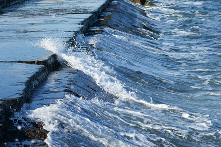 waves of stromy sea crashes on a pier