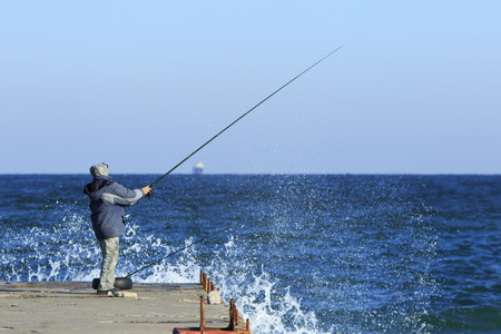fishman: Fishman stands on a pier holding his spinning with splashes of the stormy sea Stock Photo