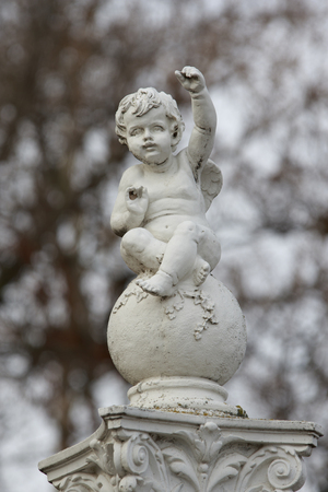 gesticulate: little boy angel sculpture sits on the ball and gesticulates