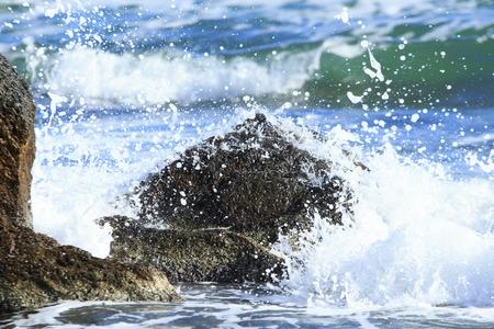 cusp: sea wave breakes on the pyramid-shaped stone