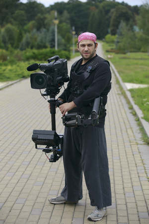 stabilization: professional cameraman with camera and stabilization system in pink bandana and with the earring Stock Photo