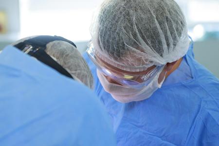 zwei unkenntliche Chirurgen arbeiten mit gebeugten Köpfen in OP-Mänteln, Masken und Hüten. Einer von ihnen ist in OP-Brille (Brille)