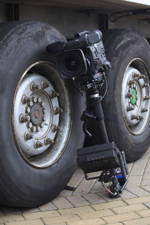 leaning on the truck: professional tv camcorder on image stabilization system leaning on the wheel of truck