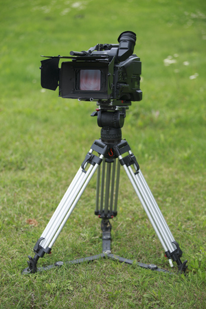 compendium: professional tv camera on tripod stands in the green field Stock Photo
