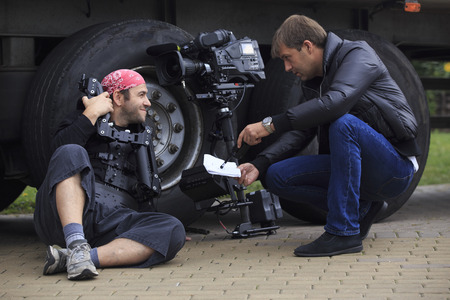 stabilization: cameraman and director discuss scene shooting sitting at the trucks wheels with professional tv-camera and stabilization system beside