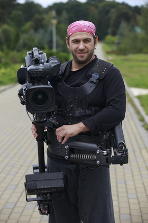 Professional cameraman with camera on stabilization system smiles Stock Photo